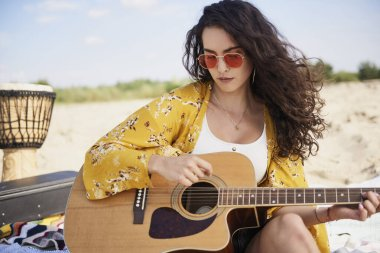 Smiling beautiful woman playing the guitar on the beach