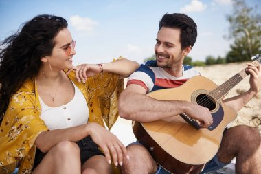 Happy man playing guitar for beautiful woman