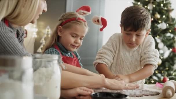 Video von Kindern und Mutter beim Ausschneiden von Lebkuchen. Aufnahme mit roter Heliumkamera in 8K.