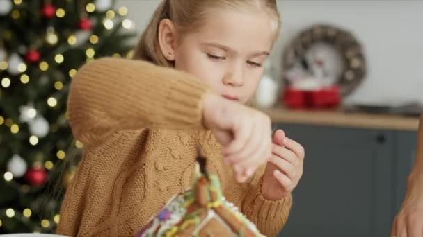 Video von niedlichen Mädchen dekorieren Lebkuchenhaus. Aufnahme mit roter Heliumkamera in 8K.