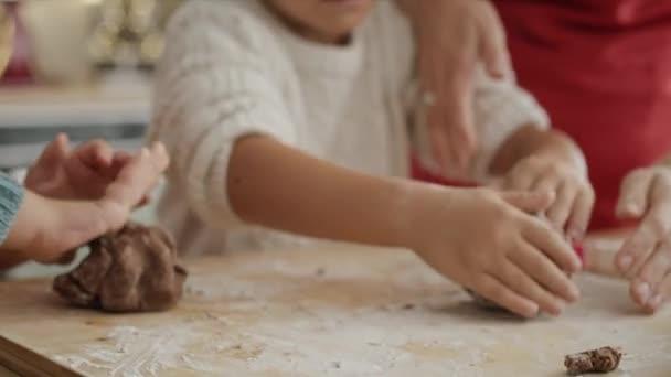 Handheld-Video von Kindern beim Zubereiten von Plätzchen mit Lebkuchengebäck. Aufnahme mit roter Heliumkamera in 8K.