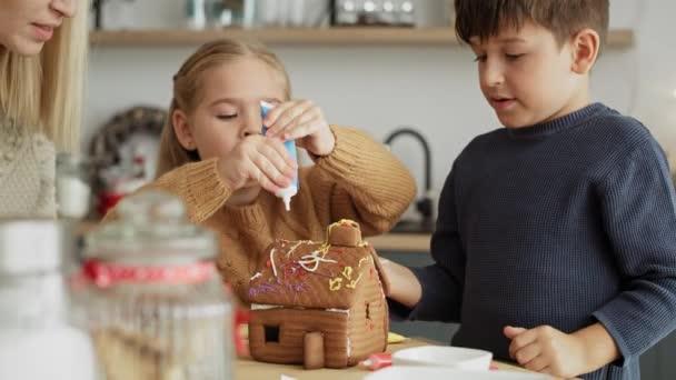 Video von fröhlichen Kindern, die ihr selbst gebackenes Lebkuchenhaus dekorieren. Aufnahme mit roter Heliumkamera in 8K.
