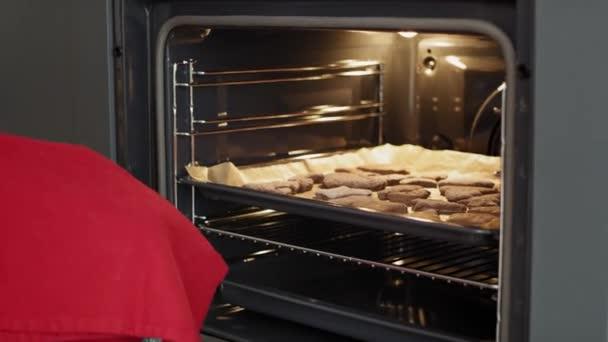Video einer Frau, die selbst gebackene Lebkuchen aus dem Ofen holt. Aufnahme mit roter Heliumkamera in 8K.