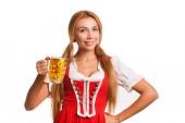 Studioporträt einer umwerfend sexy Oktoberfest-Kellnerin, die in die Kamera lächelt und freudig mit einem Bierkrug auf weißem Grund posiert. Bayerin in Tracht feiert mit Bier in der Hand