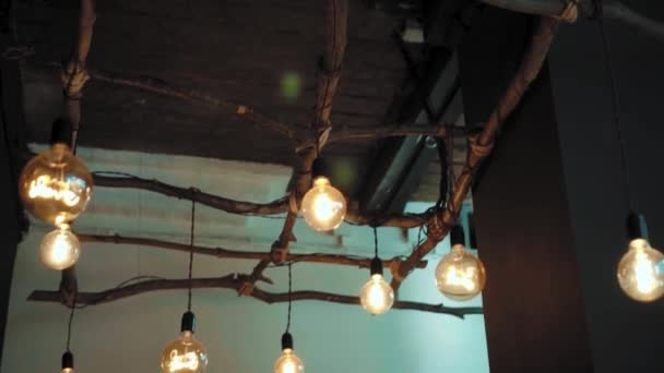 Large round decorative lamps with filament incandescent hanging on wires tied to wooden frame
