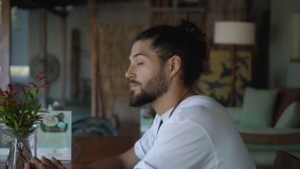 Der junge gutaussehende europäische Typ Brünette mit langen Haaren sitzt allein in einem leeren Café und dreht den Kopf und blickt nach vorn, als ob er eine vertraute Person getroffen hätte