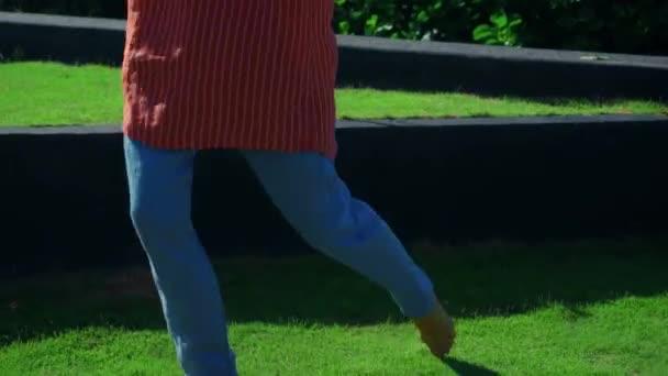 Egy fiatal lány kék nadrágban mezítláb sétál a természetben a zöld fű mentén.