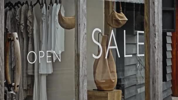 Bílý text na skleněném okně obchodu s nápisem prodej