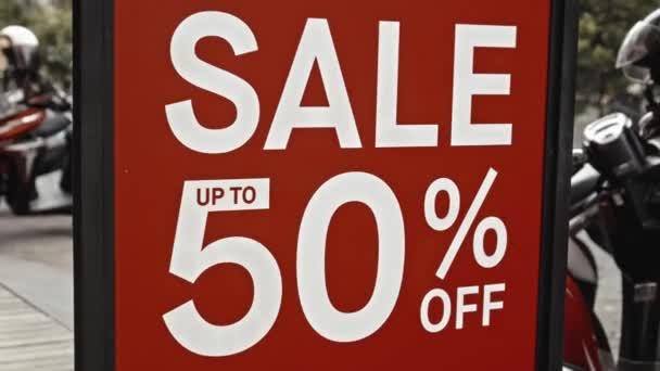 Červená cedule visící na skleněném okně s nápisem prodej až 50% sleva