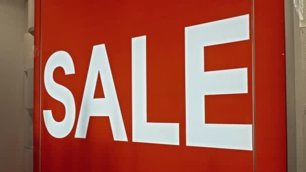 Weißer Text auf der roten Tafel im Schaufenster des Geschäfts mit der Aufschrift Verkauf