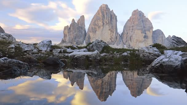 Morning in the Dolomites. Three mountain peaks and reflections in a small lake
