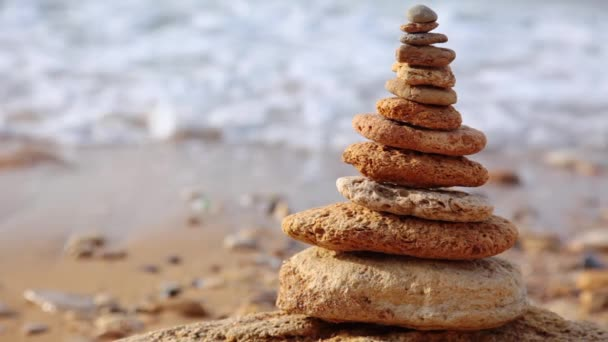 Morning surf on a wild beach in defocus. A pyramid of pebbles in the foreground. Seamless loop