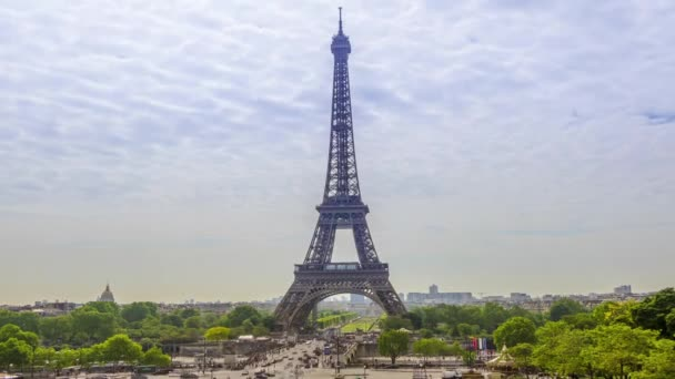 France. Paris. Summer day. Traffic people and cars under the Eiffel Tower. Clouds run quickly across the sky. Time lapse
