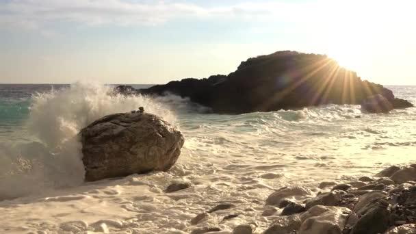Napsütéses reggel a sziklás parton. Egy hullám tör neki egy sziklának, sok-sok csobbanással. Lassú mozgás.