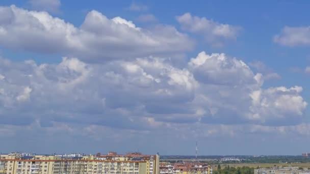 Slunečný letní den nad střechami města. Na modré obloze se rychle rozbíhají mraky. Panorama. Časová prodleva