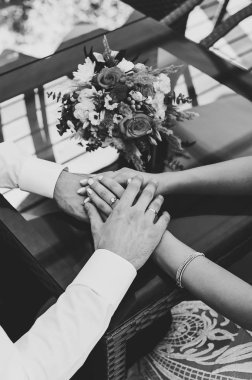 Bride and groom holding hands near stylish wedding bouquet