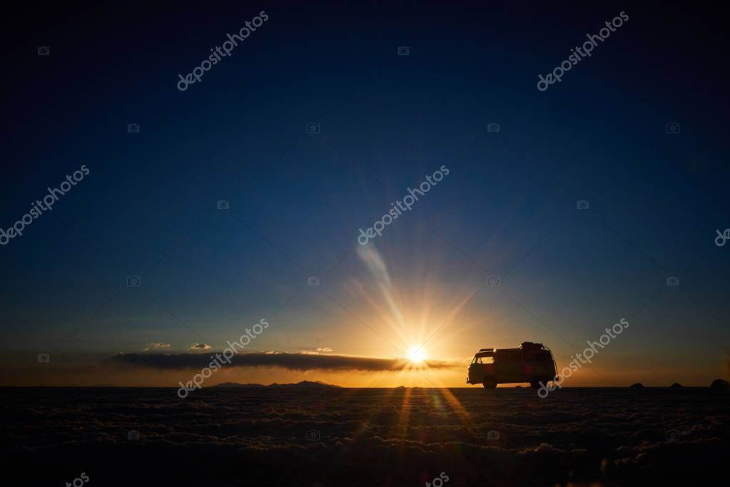 Romantic scene of the sunset blue color in the salar de uyuni, in backlight with a van vw. Salar de Uyuni. Bolivia