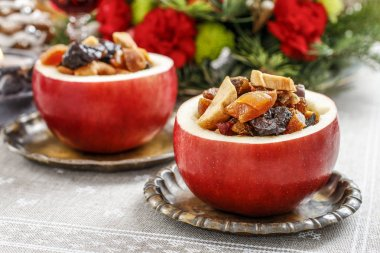 Red christmas apple stuffed with dried fruits in honey. Festive dessert