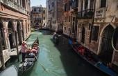 Turisté v gondole plovoucí kanálem v Benátky, Itálie