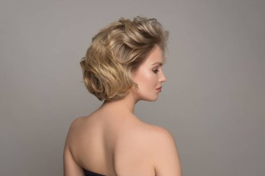 Blonde Girl with Elegant and shiny Hairstyle. Beautiful Model Woman with Curly Hairstyle. Care and Beauty Hair products. Perfect Make-Up