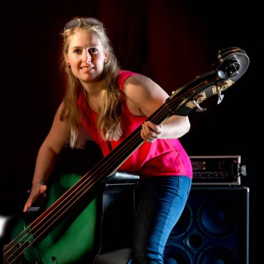 Female musician with red shirt plays on a double bass