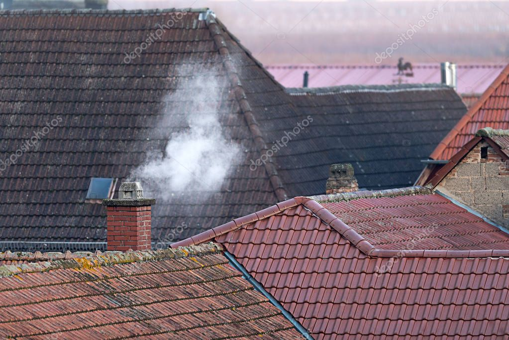 Roofs of an old village with a smoking chimney
