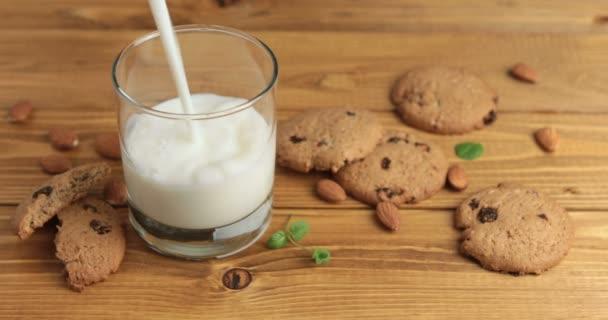 Zpomalený záběr nalil sklenku mléka na dřevěné pozadí