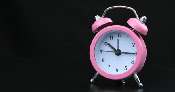Růžové hodiny s černými čísly a šipkami na černém pozadí, časová prodleva