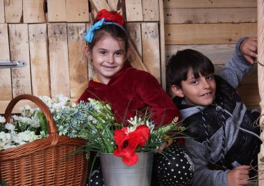 Brother and sister with many flowers on wooden background.