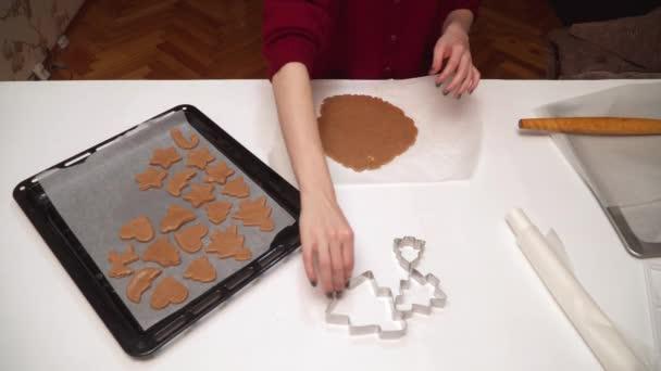 Közelkép a lányok kezét, hogy házi mézeskalács cookie-kat. Karácsonyi sütés. Tésztát és a forma, a gyömbér cookie-k. Lány tekercs tésztát és vágott adatok cookie cutter
