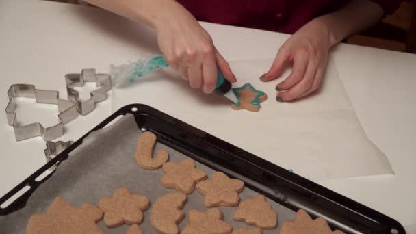 Dívka zdobí domácí perník, které soubory cookie se barevná glazura zblízka. Vánoční pečení