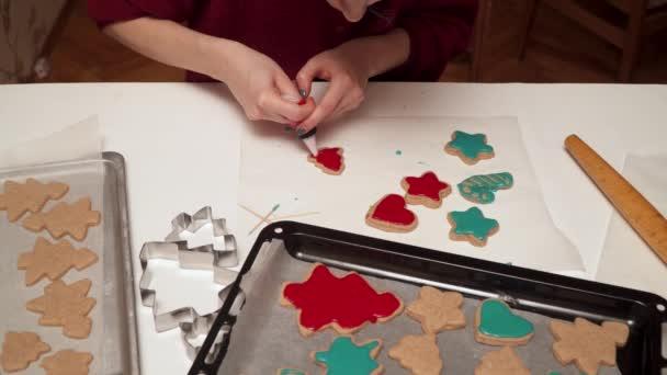 Lány díszíti házi mézeskalács cookie-kat, színes mázzal közelről. Karácsonyi sütés.