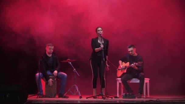 Hudební kapela na jevišti v červené světlo a kouř v pozadí. Tři hudebníci - dívka zpěvák, bubeník a kytarista provádět hudbu během show.