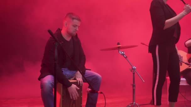 Teljesít egy dal rá eső részét a színpadon, a vörös fény, és füst, háttérben a show alatt zenekar dobosa.
