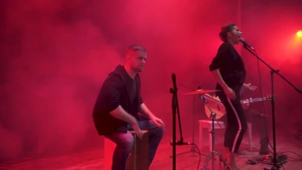 A zenekar a színpadon, a vörös fény, és füst háttérben teljesítő. Három zenész - énekes lány, dobos és gitáros zenélt a show alatt.