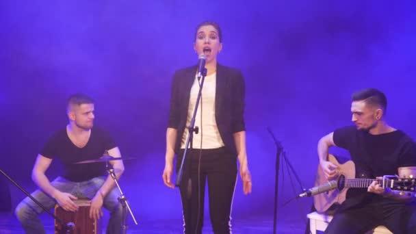 Teljesít a színpadon, a fény, és füst, háttérben a kék koncert zenekar. Három zenész - énekes lány, dobos és gitáros zenélt a show alatt.