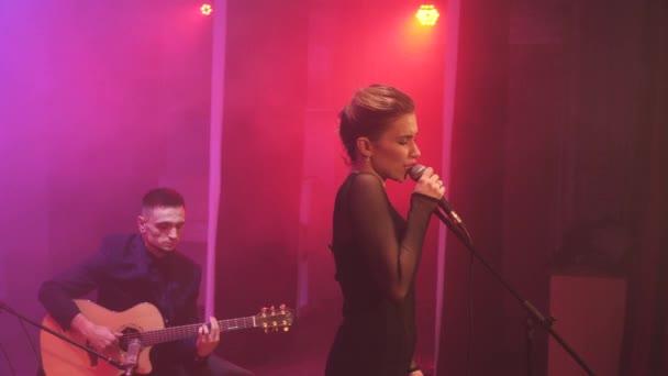 Hudební kapela na jevišti v různých barev světla a kouř v pozadí. Tři hudebníci - dívka zpěvák, bubeník a kytarista provádět hudbu během show.