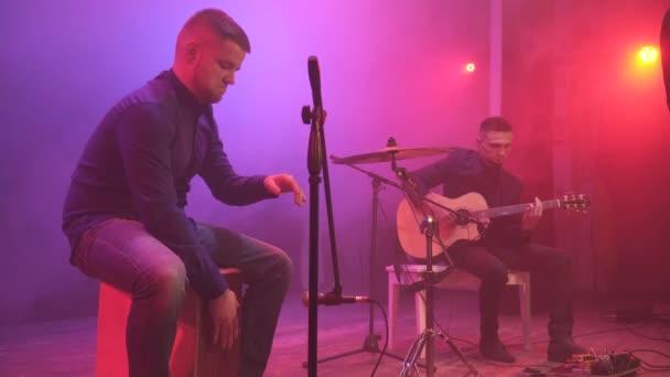 A zenekar teljesít a színpadon, a különböző színű fény, és füst a háttérben. Három zenész - énekes lány, dobos és gitáros zenélt a show alatt. Steedicam repülni