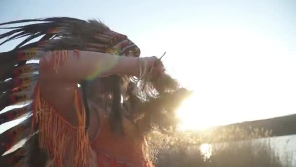 Schöne Mädchen in indianischer Kopfbedeckung und Kostüm mit buntem Make-up mit indianischem Gras in ihren Händen wirbeln in rituellem Tanz. Sorghastrum nutans