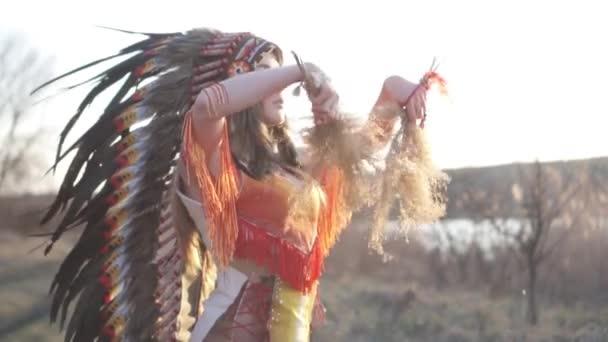 Schöne Mädchen in indianischer Kopfbedeckung und Kostüm mit buntem Make-up schüttelt indisches Gras in ihren Händen und atmet tief durch.