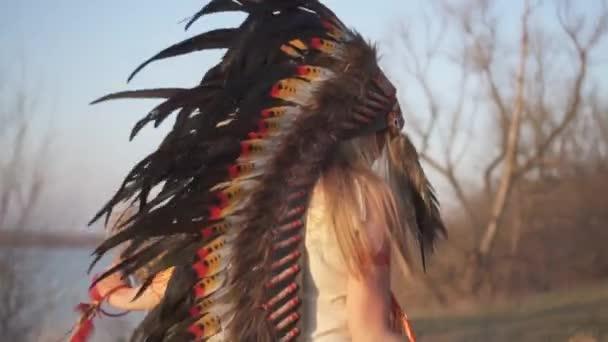 Schöne Mädchen in indianischer Kopfbedeckung und Kostüm mit buntem Make-up beim Ritualtanz am Sonnenuntergang mit indianischem Gras in den Händen.
