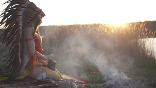 Gyönyörű lány indián fejdísz és jelmez színes smink tartja egy tál egy habarcs a kezében, és zúzás bogyók és por