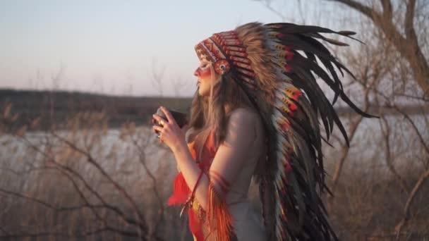 Schöne Mädchen in indianischer Kopfbedeckung und Kostüm mit buntem Make-up, das einen Steinmörser hält und daraus trinkt