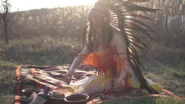 Schöne Mädchen in indianischen Kopfschmuck und Kostüm sitzt auf der und führt ein Ritual wirft Puder auf der Spitze