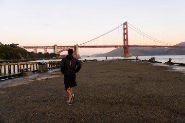 SAN FRANCISCO, USA - OCTOBER 12, 2018: A man running at sunrise on the Torpedo Wharf, San Francisco