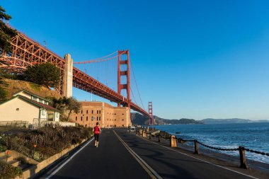 SAN FRANCISCO, USA - OCTOBER 12, 2018: Woman running at Fort Point with the Golden Gate Bridge in the background