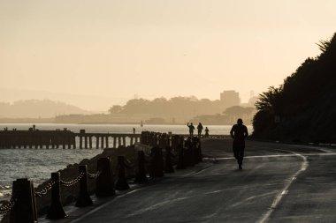 SAN FRANCISCO, USA - OCTOBER 12, 2018: People running at sunrise near Torpedo Wharf and Fort Point San Francisco