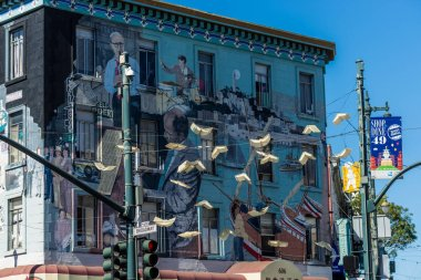 Beautiful graffiti mural on the wall and some flying books hanging outside North San Francisco