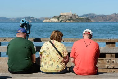 Tourists sitting on a bench with views of the island and Alcatraz prison in the background from Pier 39 in San Francisco