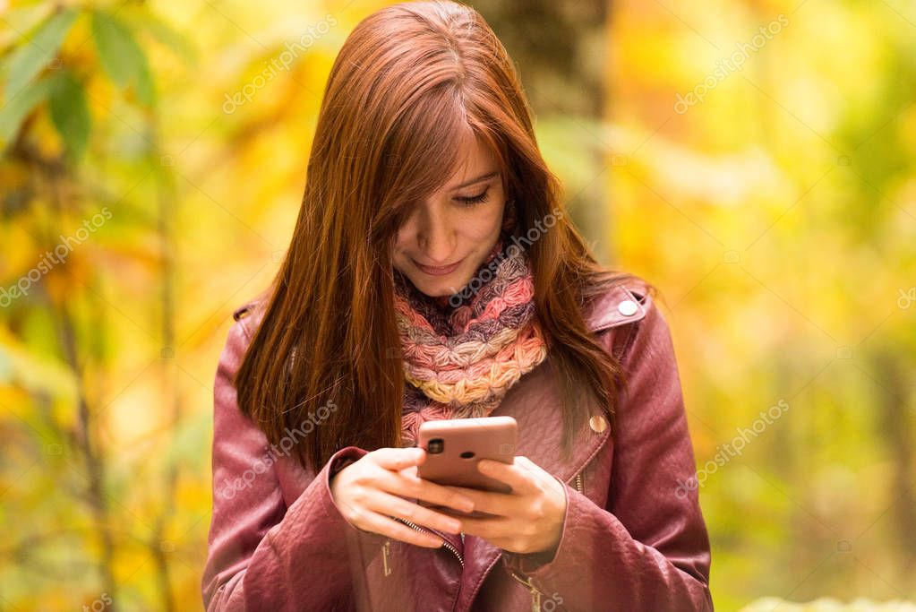 A young red-haired woman look at her mobile phone in the forest